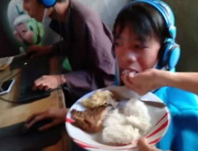 La madre le da de comer en la boca el chico.
