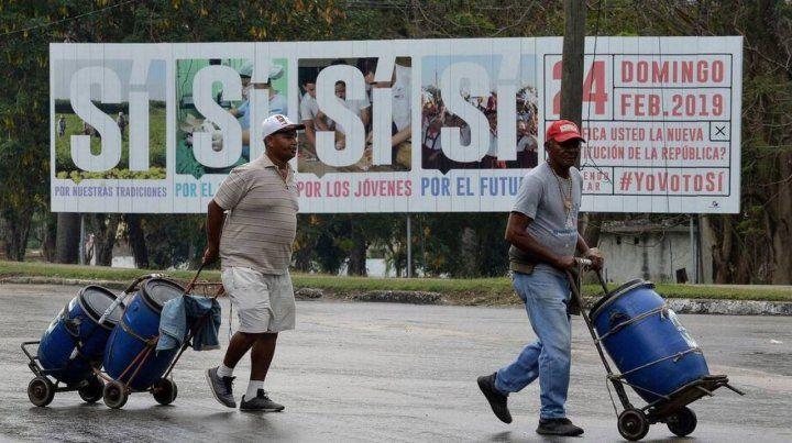Consulta. Dos cubanos caminan frente a un cartel que promueve el sí a la nueva Carta Magna.