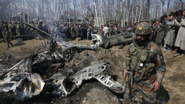 Disputa. Un soldado indio cruza frente a los restos de un caza derribado.