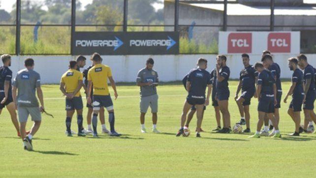 Centro de atención. Ferrari observa sus apuntes mientras los futbolistas lo rodean a la espera de las indicaciones. El Loncho dijo que ante Belgrano es una final.