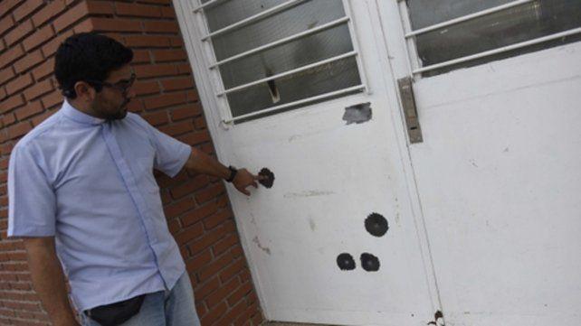 Balazos. El sacerdote de la parroquia María Reina muestra los impactos en la puerta del Colegio Paulo VI
