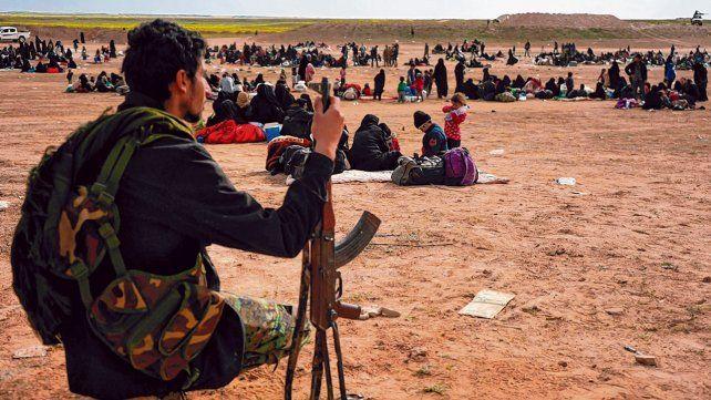 Aldea de Baghouz. Un integrante de las fuerzas democráticas custodia a las familias que fueron evacuadas del último territorio en poder de EI.