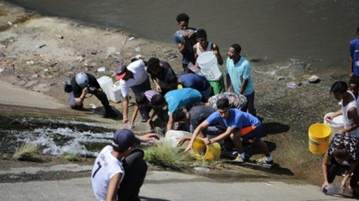 Peligro. Los caraqueños ayer recogían agua de los caños que desagotan en el río Guaire.