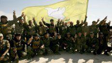 Triunfo. Los milicianos de las fuerzas apoyadas por EE.UU posan ayer en una azotea.
