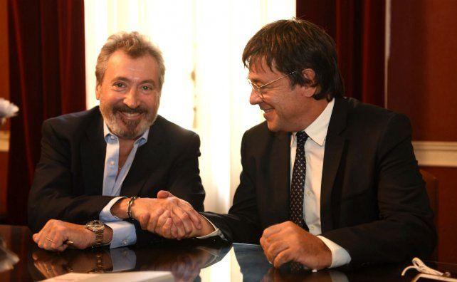 Daniel Vila y Gustavo Scaglione se saludan tras la firma de la compra.