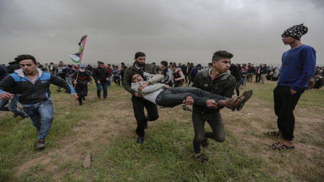 Sábado violento. Manifestantes socorren y sacan del territorio límite a uno de los heridos.