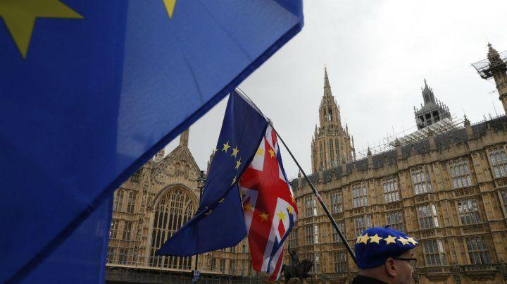Un manifestante anti Brexit exhibe sus banderas frente al Parlamento británico.