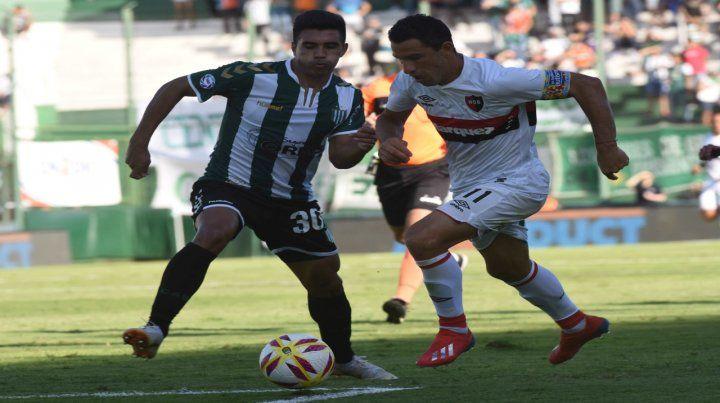 Poco juego. Maxi Rodríguez trata de superar a Jorge Rodríguez. El capitán rojinegro tuvo una tarde desdibujada y no influyó.