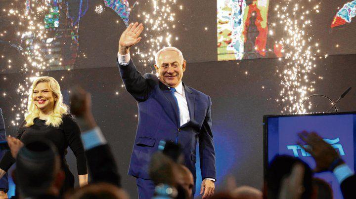 Tel Aviv. Netanyahu y su esposa Sara saludan a sus partidarios. El premier israelí aparece con mayores chances de formar gobierno.