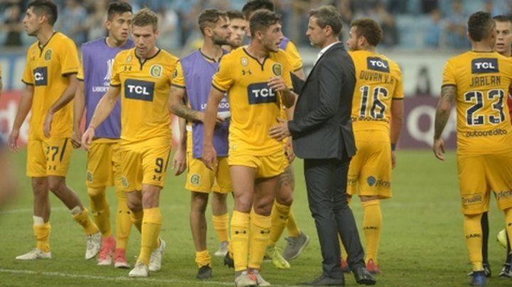 Caras largas. Los futbolistas canallas se retiran del Arena do Gremio acompañados por Cocca con la desazón por la derrota.