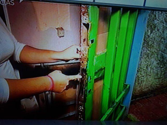 Débora muestra cómo le quedó la puerta de entrada tras la violenta entrada de los policías. (Foto: imagen de TV)