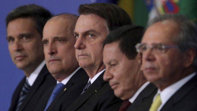 Todo mal. Bolsonaro rodeado de sus principales ministros durante una ceremonia en Brasilia.