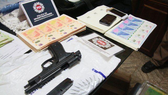 Preparados. Las planchas de billetes para cortar y un arma incautada.