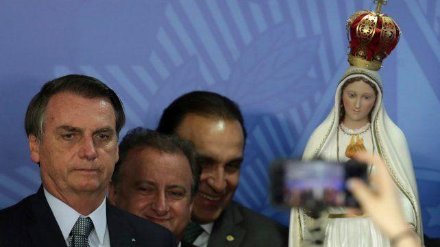 Cuestionado. El mandatario brasileño posó ayer junto a una estatua de la Virgen de Fátima durante una ceremonia religiosa.