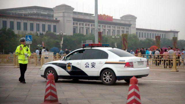 Sitio histórico. Un oficial de seguridad camina cerca del móvil policial mientras detrás se esparce el público.