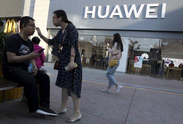 ¿Y ahora? Una pareja ante un negocio de Huawei en Pekín.