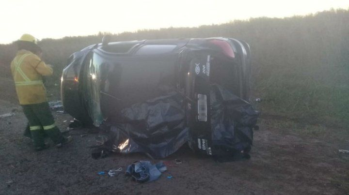 Bomberos trabajan sobre el auto que terminó volcado esta mañana