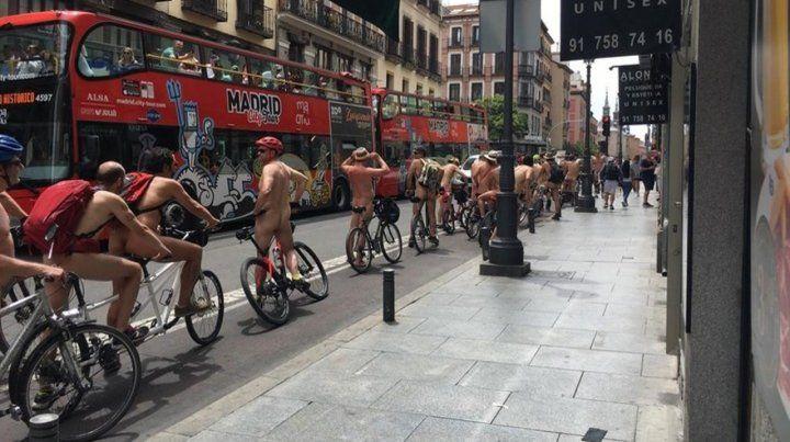 Desde un ómnibus turístico fotografían a los ciclistas desnudos.