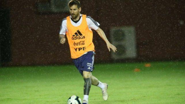Con su mejor amiga. Messi entrenó ayer bajo una llovizna intensa.