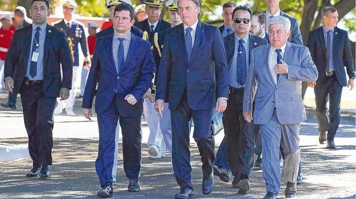 Sergio Moro (segundo a la izquierda) y Jair Bolsonaro caminan juntos en un predio militar de Brasilia donde el ex juez fue condecorado.