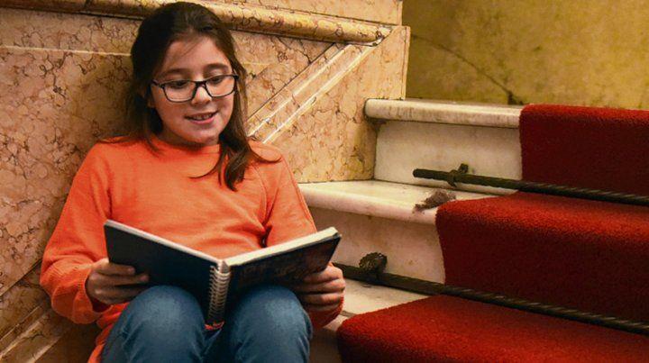 La pequeña Dolores escribe los manuscritos de su novela en un cuadernito.