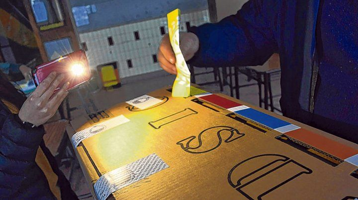 En tinieblas. Los rosarinos que madrugaron debieron iluminarse con el celular para poder emitir su voto.