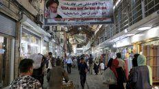 vida diaria. El gran bazar de Teherán. Una pancarta del régimen arenga al público que sufre la carestía, agravada por las sanciones de EEUU.