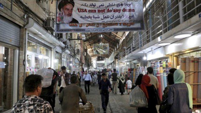 vida diaria. El gran bazar de Teherán. Una pancarta del régimen arenga al público que sufre la carestía