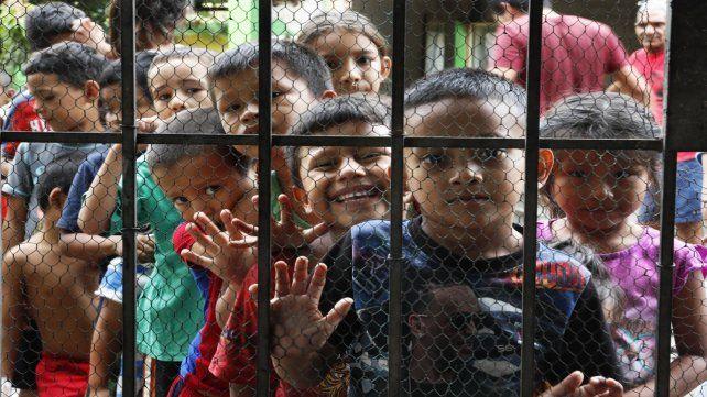 Chicos centroamericanos esperan recibir comida en un centro de refugiados en Tapachula