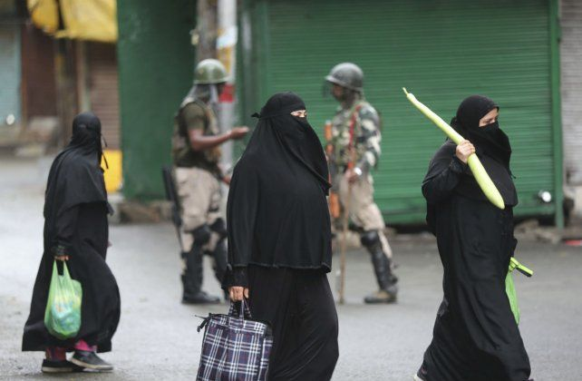 Control. Mujeres islámicas cruzan un control militar en Srinagar.
