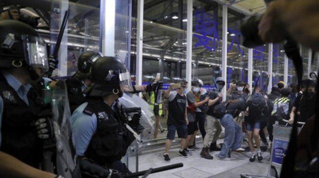 Aeropuerto. La policía hongkonesa lanza gas pimienta a algunos de los manifestantes que mantienen paralizada a la terminal internacional.