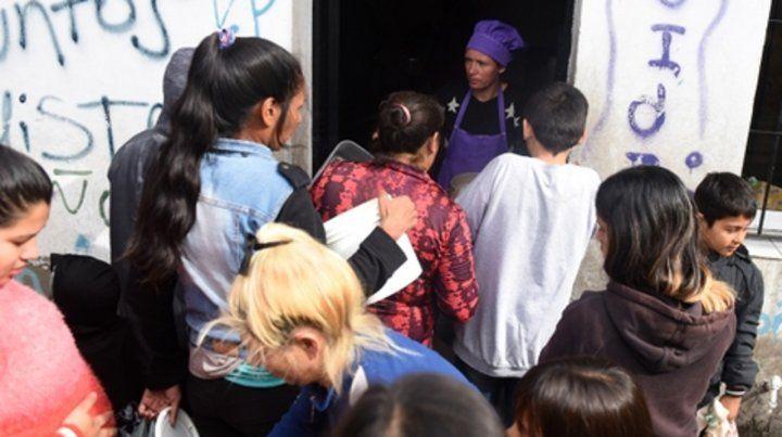 Asistencia alimentaria. Un grupo de personas aguarda la entrega de bolsones en la puerta de un comedor barrial.