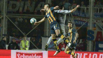 El defensor canalla Matías Caruzzo y el atacante cuervo Díaz saltan con toda la potencia ante la atenta mirada de Barbieri.