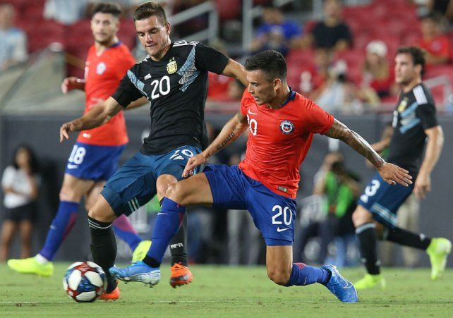 Lo Celso disputa el balón con el chileno Aranguis. El talentoso volante rosarino tuvo un golpe en ese partido que lo mantendrá fuera de las canchas por espacio de casi dos meses.