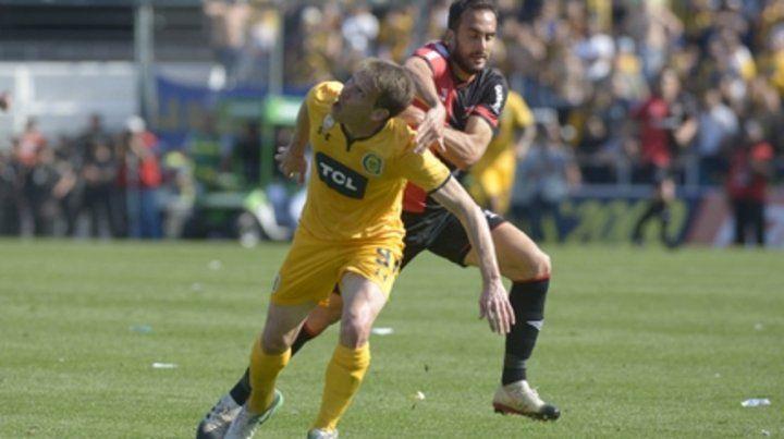 Juego aéreo. Riaño busca la pelota seguido de cerca por Gentiletti. El delantero canalla se impuso en el duelo.