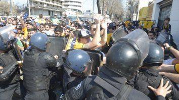 Disturbios. La policía echa mano a los escudos para detener a los hinchas indignados por no poder entrar.