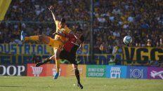 Máximo esfuerzo. Angelo Gabrielli salta para ganarle la posición a Pereyra. El uruguayo cumplió en el clásico.