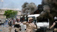 Puerto Príncipe. Los policías se mueven alrededor de un autobús propio, incendiado por manifestantes enfrente del Parlamento.