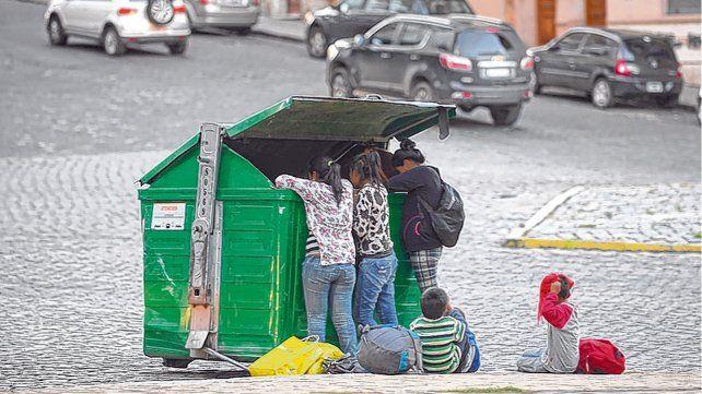 Triste postal. Un grupo de mujeres y niños busca alimentos y ropa en un contenedor de basura.