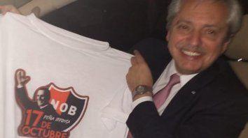 Alberto Fernández, anoche cuando recibió la camiseta de Newells y la remera leprosa de la Peña 17 de Octubre.