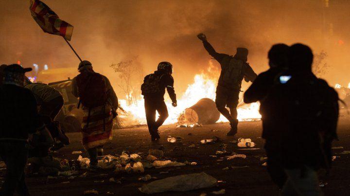 Manifestantes arrojan objetos contra la policía de Cataluña.