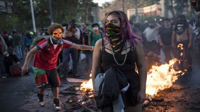 En lucha. Adolescentes enmascarados junto a una barricada.