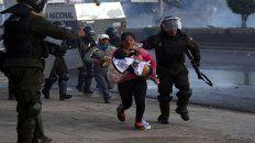 Una mujer intenta poner a salvo a su hijo en medio de la violenta represión.