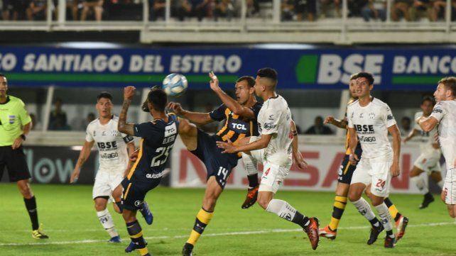 El defensor canalla Diego Novaretti rechaza con toda la fuerza ante la arremetida del zaguero Salomón.