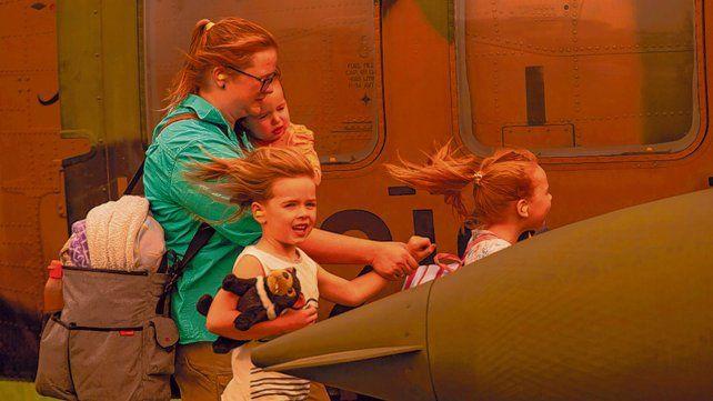 peligro. Una madre y sus hijos abordan un helicóptero en Australia