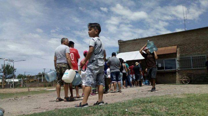 La cola del agua. Grandes y chicos esperan su turno para poder retirar un bidón de agua potable del tanque que abastece al barrio.