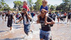 Peligro. Padres jóvenes cruzan a la carrera el río Suchiate con sus hijos sobre los hombros.