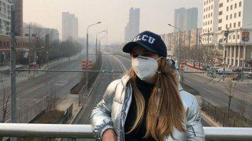 Bianca en un puente sobre una avenida principal desierta de Beijing.
