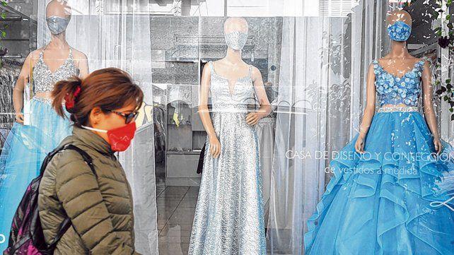 Nuevos tiempos. Una mujer cruza por delante de una vidriera de alta costura en pleno centro.