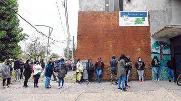 beneficiarios a la espera. Pese al mal tiempo, se formó una hilera frente a la escuela de Sabin al 1100.